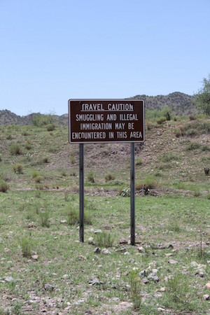 "Sign reading ""Travel Caution: Smuggling and illegal immigration may be encountered in this area"""